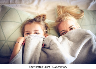 Portrait mother and daughter hide under blanket on a bed.
