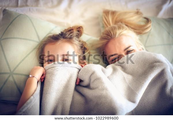 ベッドの上の毛布の下に隠れる、母と娘のポートレート。