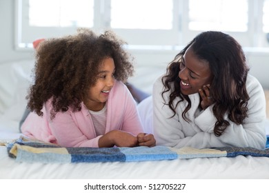 Portrait of mother and daughter lying on bed at home