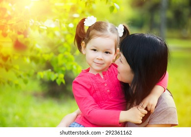 Portrait of mother and daughter. Mommy hugging with little child in summer green park on sunny day. Happy family concept. Beautiful smiling girl looking at camera. Horizontal color photo.