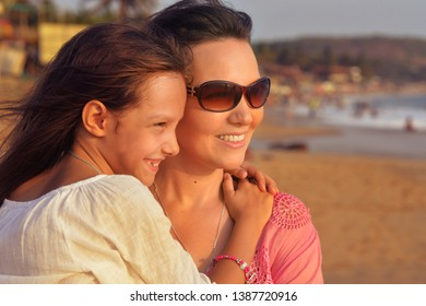 Portrait of mother with daughter on beach