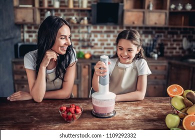 portrait of mother and daughter preparing smoothie using blender on the kitchen