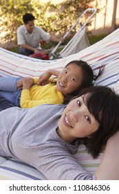 Portrait of mother and daughter relaxing on hammock with father in the background
