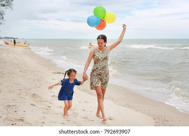 Portrait of Mother and daughter running on beach with colorful balloons in mother hand. Holiday concept.