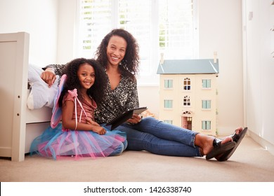 Portrait Of Mother With Daughter Sitting On Bed In Childs Bedroom Using Digital Tablet Together