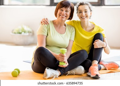 Portrait of a mother and daughter in sports wear sitting together after the training indoors