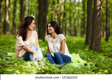 Portrait of mother and daughter talking, sitting on a blanket at a picnic