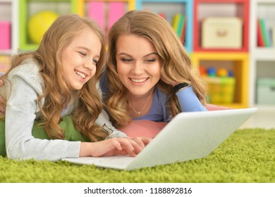 Portrait of mother and daughter using laptop