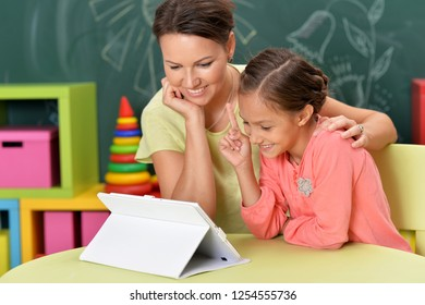 Portrait of mother and daughter using tablet together