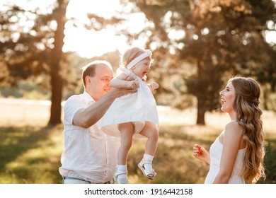 Portrait of a mother, father holds, throws up and spins the daughter on hands walking on nature on summer day vacation. Mom, dad and girl playing in the park. Concept of happy family