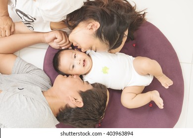 Portrait of mother and father kissing their 5 months old baby, top view point