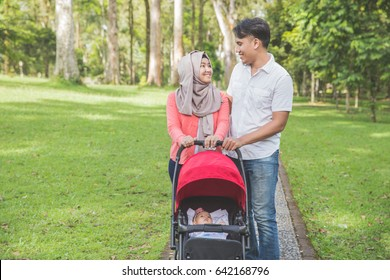 Portrait of mother and father pushing baby stroller in park