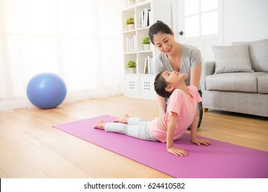 portrait of mother gently teaching her small girl his first yoga notions careful near kids body helping daughter finished action in the fitness class at school.