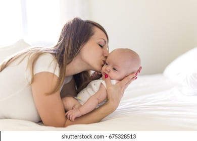 A Portrait of mother with her 3 month old baby in bedroom
