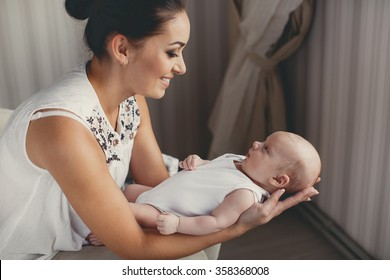 Portrait of a mother with her 3 months old baby. Mother holding head of her newborn son in hands. The baby on hands at mum. Loving mother hand holding cute sleeping newborn baby.home portrait. love