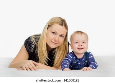 A portrait of a mother and her baby boy lying on the floor and smiling over white background