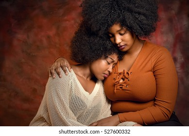 Portrait of a mother and her daughter cuddling. Upset family against a red background.
