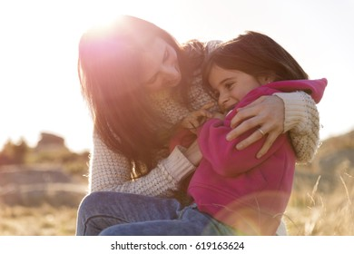 Portrait of mother and her daughter embracing and playing in the bright light of the sun, happy family.