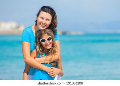 Portrait of mother and her daughter in sunglasses having fun on tropical beach