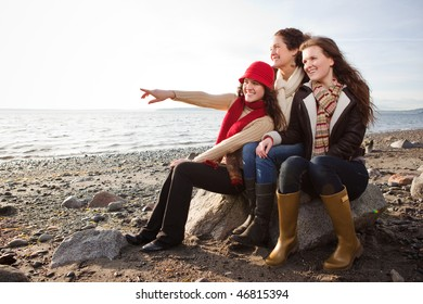 A portrait of a mother and her daughters on the beach