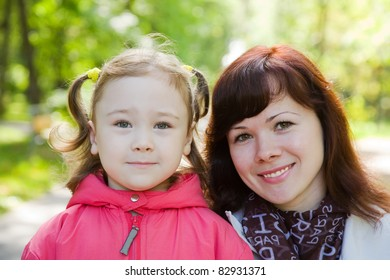 Portrait of mother with her girl in autumn park
