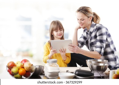 Portrait of mother and and her little daughter cooking together at home. Beautiful mom holding in her hand a digital tablet and reading recipe while making some cookies with her adorable little girl.