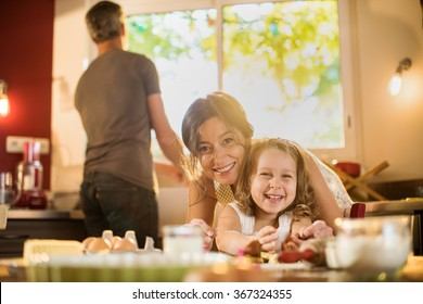 Portrait of a mother and her smiling four years old blonde daughter cooking in a kitchen. They are looking at camera, posing on a table full of ingredients The dad is doing the dishes. Shot with flare