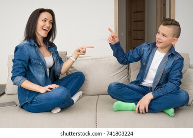 Portrait of mother and her son sitting on sofa at home