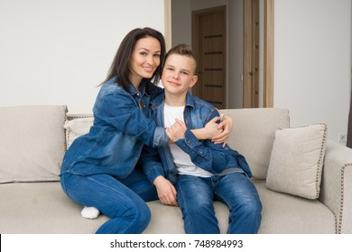 Portrait of mother and her son sitting on sofa at home, hugging and smiling