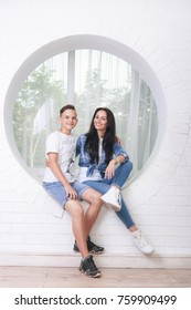 Portrait of mother and her son sitting in white room interior, smiling and looking at camera