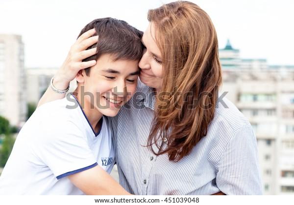 Porträt einer Mutter mit ihrem Sohn Teenager. Zärtlichkeit, Liebe, multinationale Familie