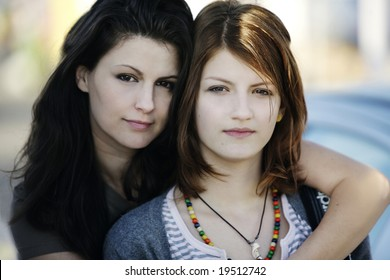 Portrait of mother and her teen daughter looking at the camera