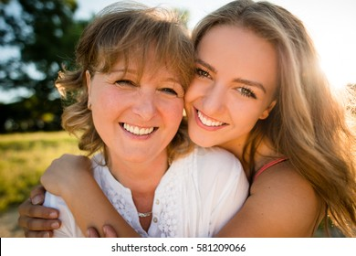 Portrait of mother and her teenage daughter outdoor in nature with setting sun in background