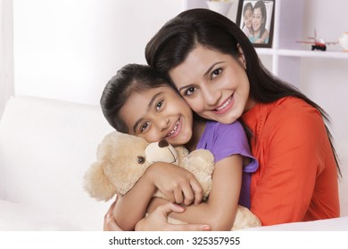 Portrait of mother hugging daughter with stuffed toy
