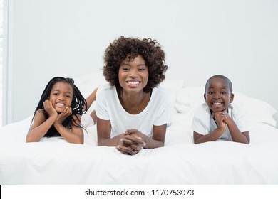 Portrait of mother and kids lying on bed at home