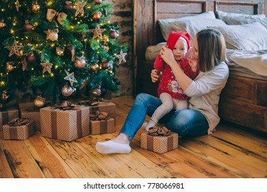 Portrait of a mother with a little baby girl on white bed in home Christmas decorated interior. A child in a New Year's sweater.