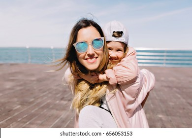 Portrait of mother with little daughter by the sea. They are loo