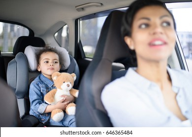 portrait of mother and little daughter driving in car together