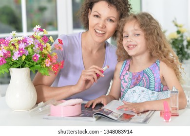 Portrait of mother with little daughter with magazine