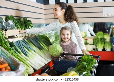 Portrait of mother with little girl purchasing shallot and celery