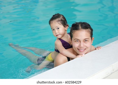 Portrait of mother and little girl in swimming pool