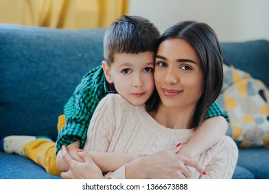 Portrait of mother and little son hugging smiling indoors.