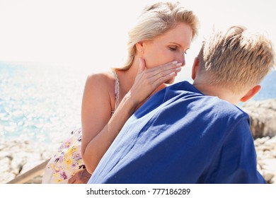 Portrait of mother and son bonding together by blue sea sunny holiday destination beach, whispering in ear, talking secret conversation, sharing outdoors. Family enjoying travel recreation lifestyle.