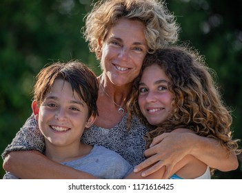 Portrait of mother, son and daughter in a garden during their holidays