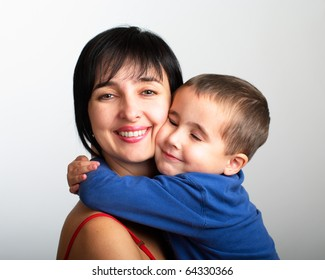 Portrait of mother and son embrace on grey gradient background