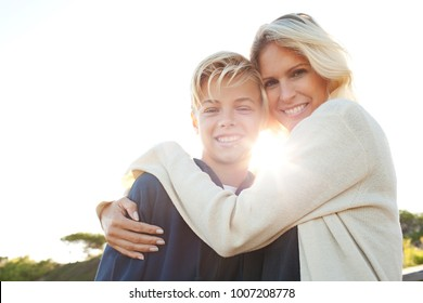 Portrait of mother and son hugging smiling with sun flare, outdoors. Happy expressions, family closeness fun. Love care, recreation lifestyle sunny exterior. Positive relations. Mum and son together.