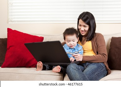 A portrait of a mother and a son using a laptop