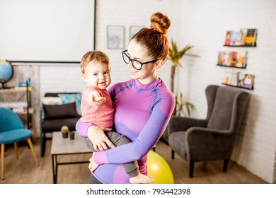 Portrait of a mother in sportswear standing with her playful baby son at home