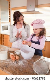 Portrait of a mother teaching her daughter how to bake in a kitchen
