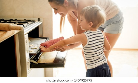 Portrait of mother with toddler son baking cookies in oven